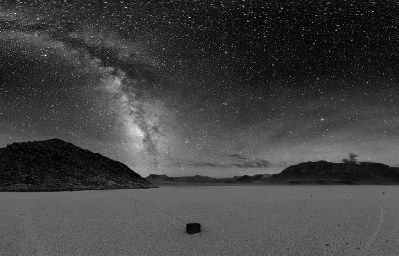 The Milky Way shines brightly in the dark sky above Death Valley. Light pollution from nearby cities casts a constant glow on the horizon.