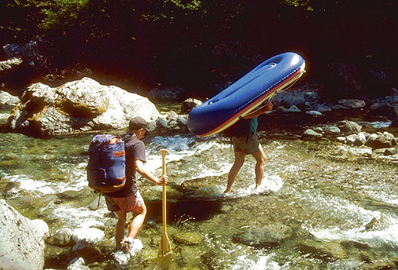 Two paddlers wading across a clear stream, one carrying a small blue raft, and one with a backpack and a paddle.
