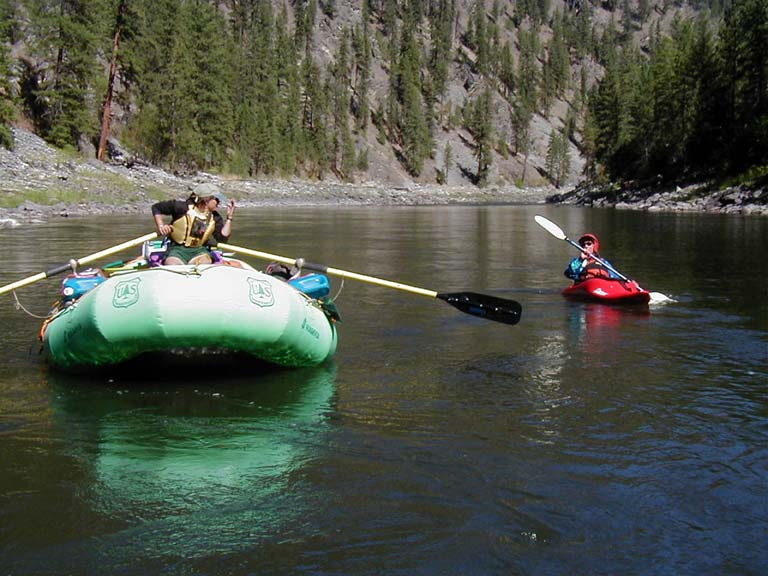 A man rowing a large green raft next to a paddler in a small red kayak, traveling through a large canyon dotted with trees.