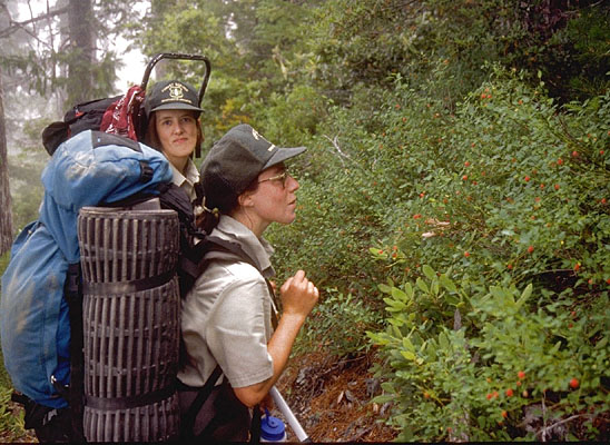 Two women with large backpacks, along a small forest trail.