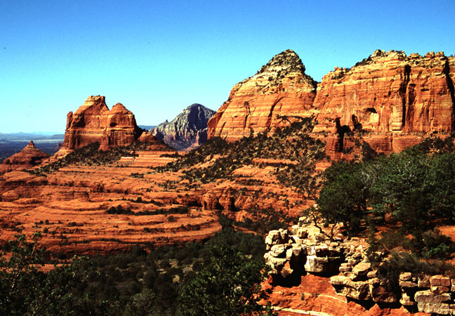 High sandstone cliffs tower above the valley floor freckled with evergreen growth and dense brush.