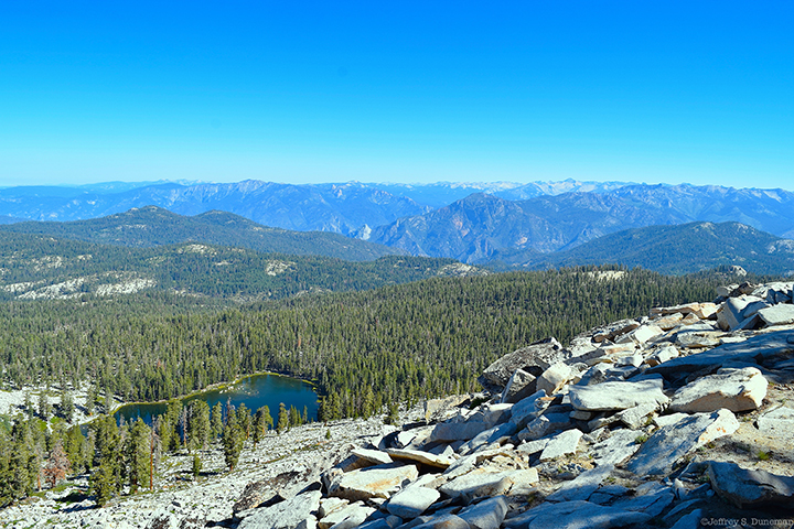 Looking down on forested hills and a small lake.