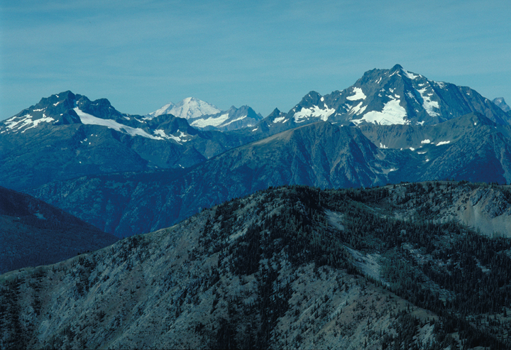 The mountains are bathed in a cool blue light. Snow can be seen on their sides and peaks.