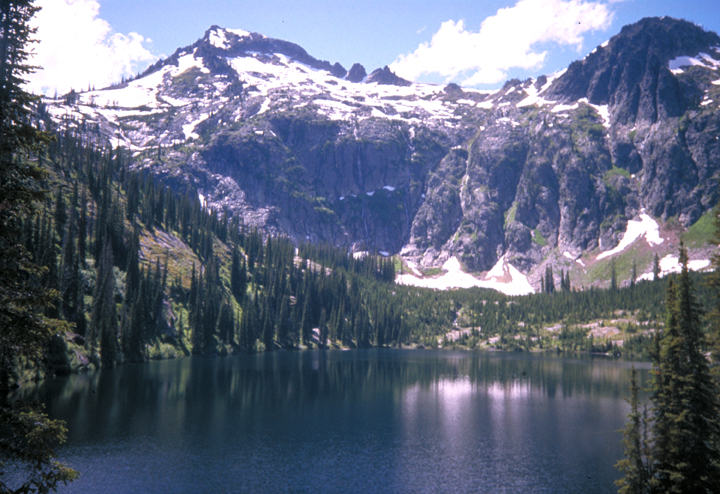 A lake rests at the foot of a snowy mountain.  The tall pine trees can be seen in hazy reflections on the water.