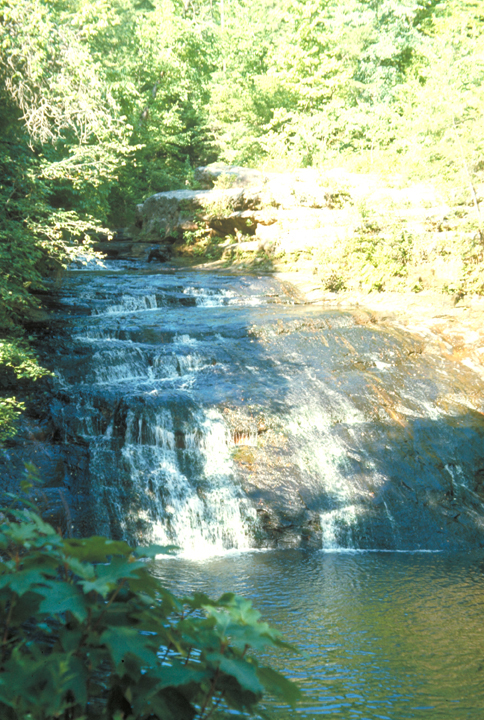 A wide waterfall skitters its way down a bluff into a deep pool.