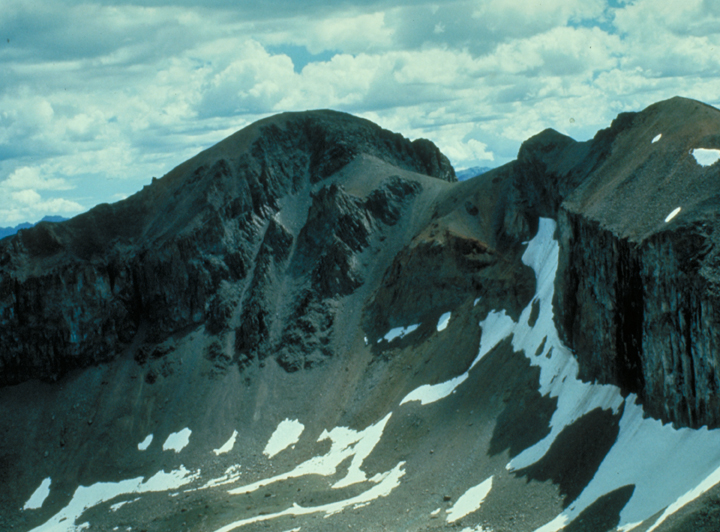 The sheer mountainside is streaked with snow, white contrasting sharply against black stone.