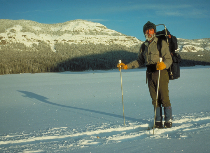A cross-country skier works his way across a snow covered landscape.  There is ice in his beard!