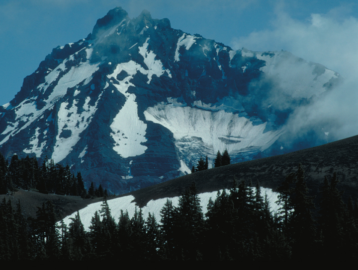One lazy bank of clouds drifts across a blue, snow covered mountain.  The silhouettes of pine trees can be seen in the foreground.