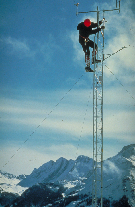 A researcher climbs a radio tower.