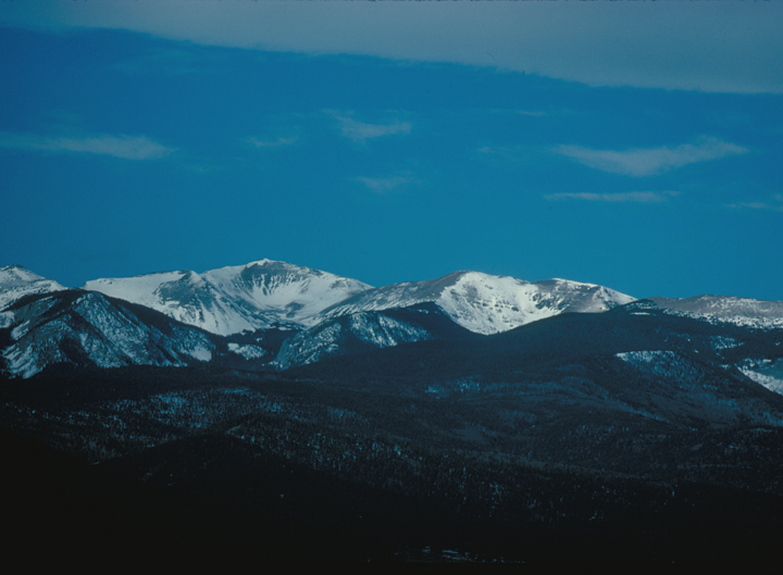 Snowy mountains sit under a crisp blue sky.  The foreground is mostly in shadow.