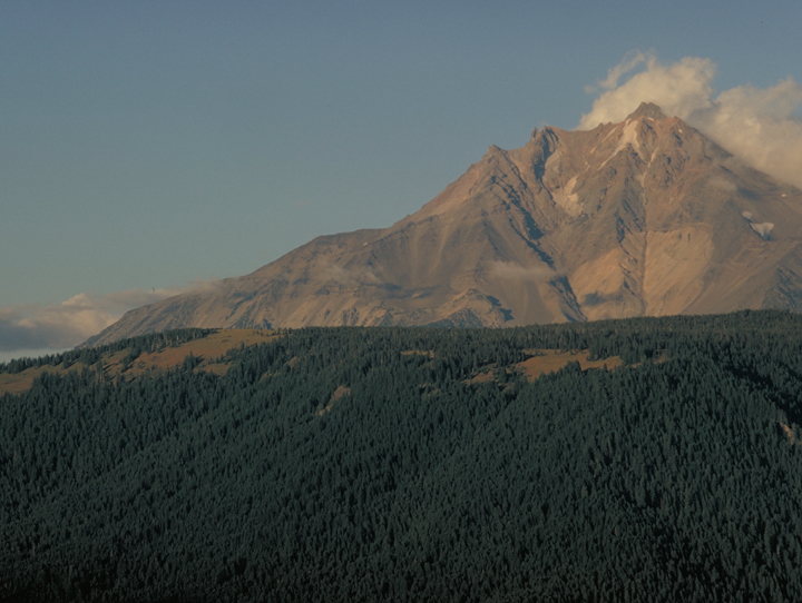 The mountain is bathed in the last light of the day and a few low riding clouds.  The forested foothills are dark.