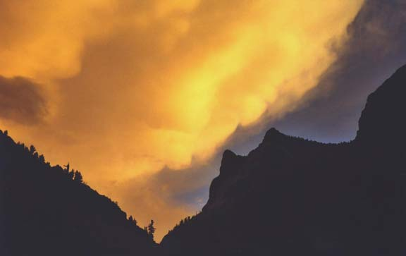 Billowing clouds drenched in golden evening light, loom high above the jagged black silhouette of a jagged peak.