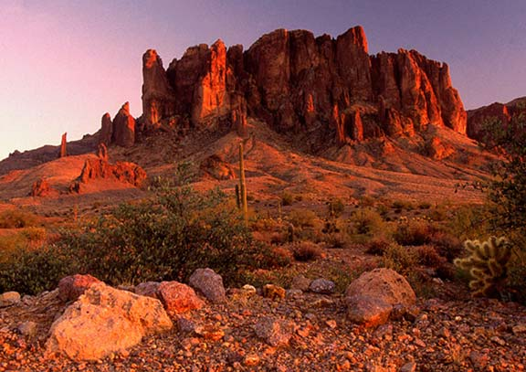 A large rock outcropping with cactus in front glows a brilliant orange in the light of the setting desert sun.