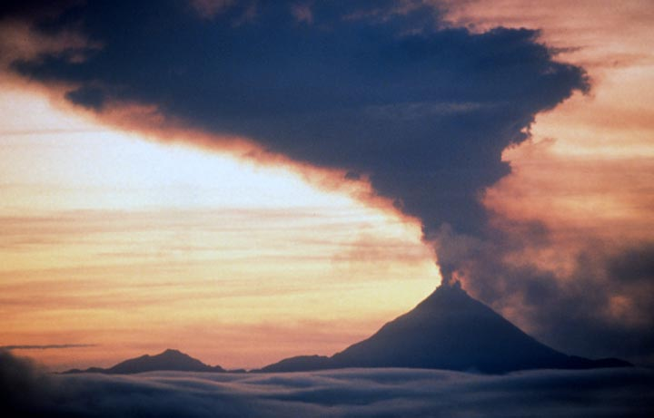 Alaskan volcano Kanaga at sunset blowing a large ploom of smoke as it juts out of a sea of underlying clouds.