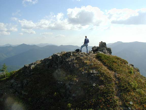 A lone hiker standing at the top of a mountain, looking out over the peaks beyond.