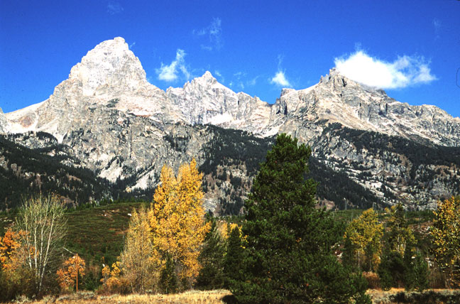 Massive peaks of jagged rock rise towards the blue sky, high above the valley floor, decorated in autumn foliage.