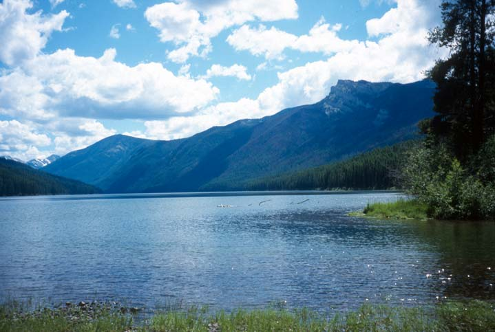 A large lake, the surface of the water reflecting the bright blue sky above. Low forested mountains rise around the perimeter of the lake.