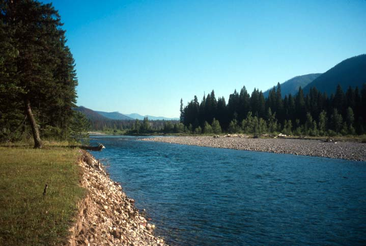 A peaceful scene of a small river, bordered by a grassy bank and an open gravel bar, at the base of a large valley.
