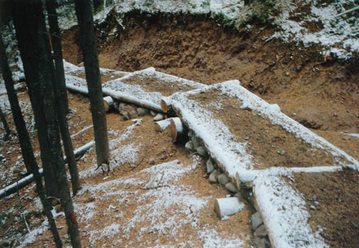 A close-up of manmade stair steps covered in snow, along an eroded section of trail.