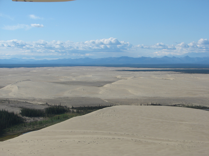 This aerial shot shows a wide sandy expanse, sliced through the center by a forested alpine valley.