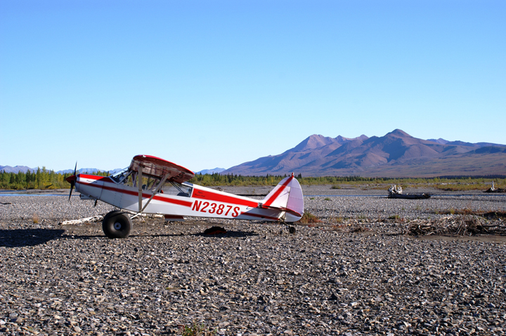 A red and white bush plane rests on a rocky creekbed.  The faint impression of a river can be seen in the background, curling its watery way in the shade of a mountain range.