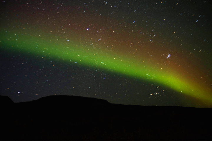 The Northern Lights paint the starry sky in vivid shades of red and green.