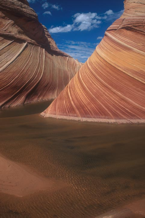 A red rock formation know as The Wave has a small body of extremely shallow water at the base of the formation. The rock edifice itself is striped with varying shades of red.