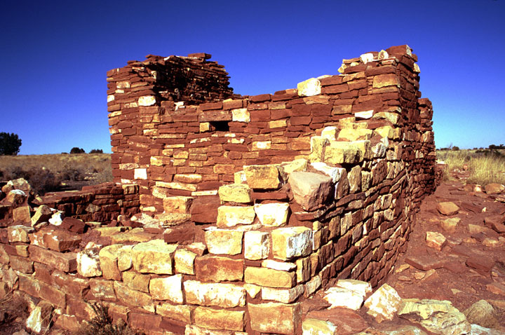 An ancient structure of stacked rock, standing against the deep blue of the sky beyond.