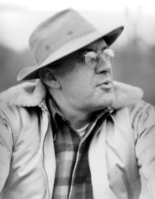 A vintage black and white photograph of a man wearing glasses and a large-brimmed hat.