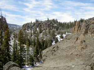 A narrow valley with a barren rocky slope on the right sweeping down to a forested slope on the left, covered in a dusting of snow.