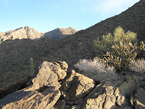 An barren rocky slope, leading up to the summit of a desert peak in the distance.