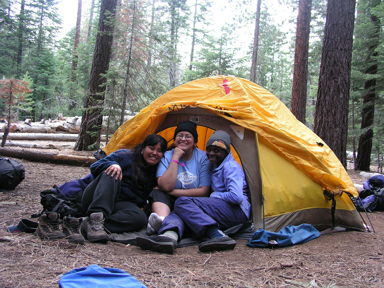 Three girls sitting in a tent