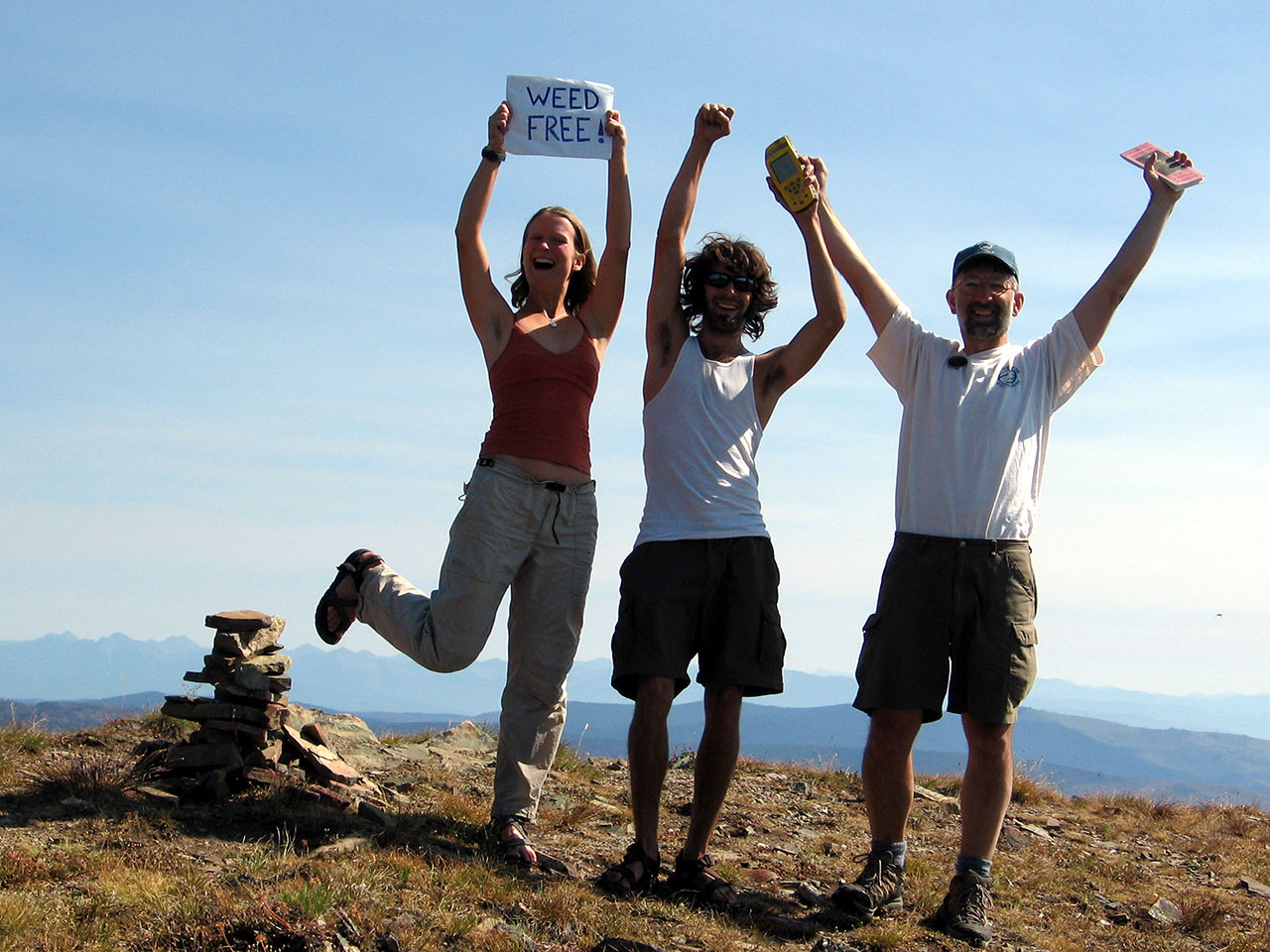 """Student wilderness volunteers hold a """"weed free"""" sign"""