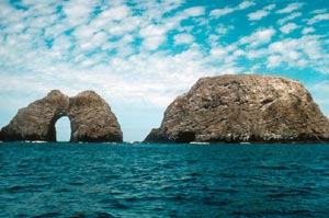 A rocky arch island rising from the blue water, under a mottled sky of blue and white.