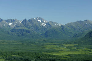 A beautiful shot of the of the foliage carpeted Ahklun Mountains and their lush green lowlands on a sunny, clear day.