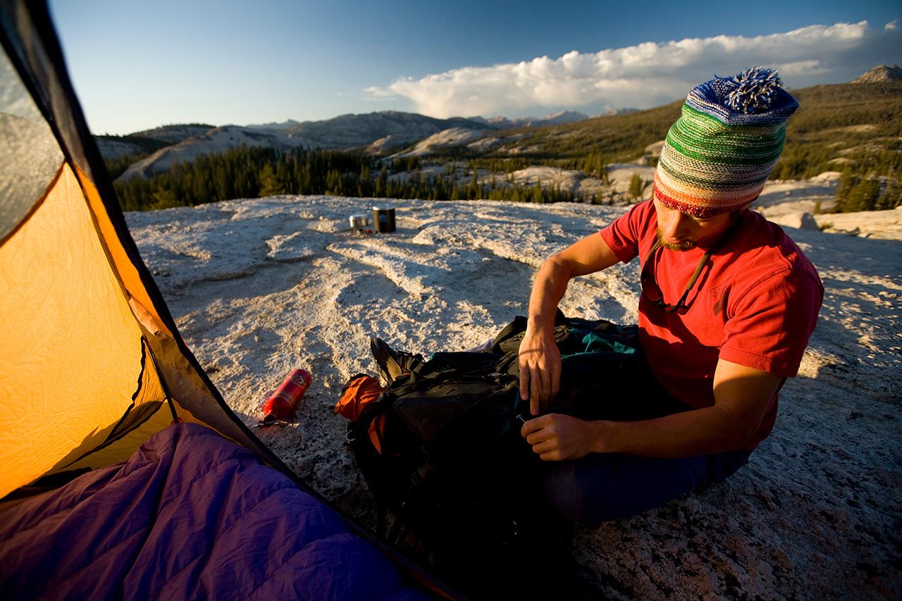 Man unpacking gear near a tent