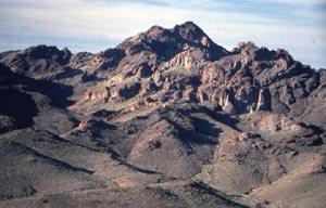 A barren desert mountain, low rocky hills fading into steep rugged pinnacles above.