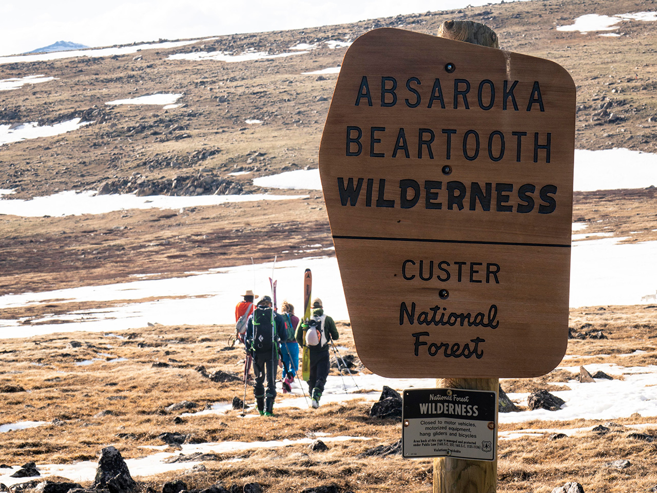 Skiers hiking behind a wilderness sign