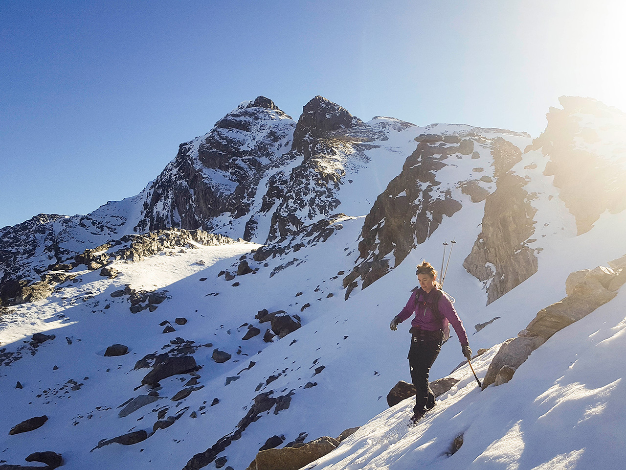 Woman hiking down a steep snowy slope